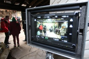 Behind the scenes image at Falconhurst- close up of the film screen, with two crew members to the left in the background.