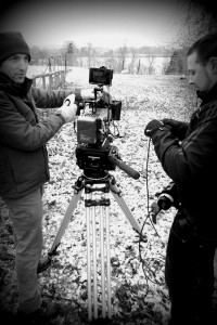 Black and white image of two cameramen talking next to a camera on a tripod. Falconhurst field in background.
