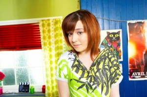 Dani Harmer in a bright green patterned top in front of a green and blue wall with posters on it