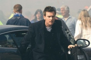 Ewan McGregor getting out of a car with lots of people behind him with debris in the air