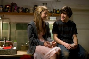 Francois Goeske and Sarah Beck as Alex and Faye sitting on a kitchen counter smiling to each other © Boxfish Films