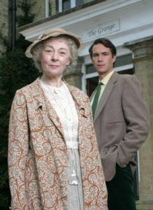 Geraldine McEwan and James D'Arcy staring into the camera in front of a period style house