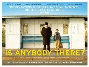 Is Anybody There? Film Poster- a man and a child stood in front of a white wooden bus shelter with a blue bench. Is Anybody There? written in yellow underneath