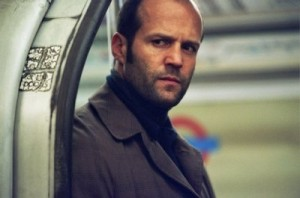 Jason Statham standing in a train door