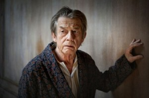 John Hurt wearing a dressing gown with one arm holding the dirty wall behind. Looking slightly distressed,.