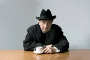 Ken Stott sat at a wooden table with a white tea cup.