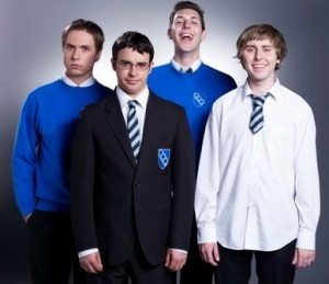 L-R Simon (Joe Thomas), Will (Simon Bird) Neil (Blake Harrison) Jay (James Buckley) stood together in school uniform looking at the camera. Plain grey background behind them