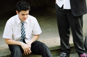 Lance (Jamie Mander) in a school uniform sitting on a pavement