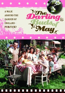 The Darling Buds of May- A walk around the garden of England text in brown, pink and green. image of the cast sitting around a large garden table smiling at the camera.