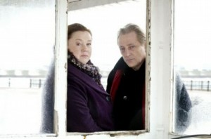 Pauline Quirke and Mark Wingett looking through a white wooden window, the sea can be seen behind them