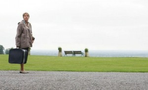 Penelope Wilton standing on the driveway at Boughton Monchelsea Place with grass and benches behind