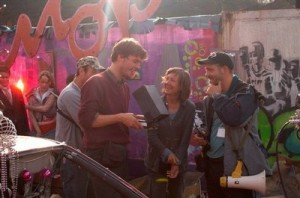 cast and crew talking in front of a graffiti wall