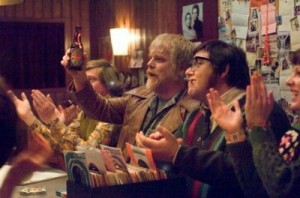 Philip Seymour Hoffman and Nick Frost at a table with other people clapping and raising their glasses off screen. Posters and paper on the wooden walls behind