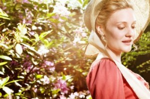 Romola Garai in a pink dress and bonnet staring towards the ground with a smile in front of bushes with flowers on