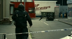 Actor walking down the street towards a red double decker bus, There is police tape behind him