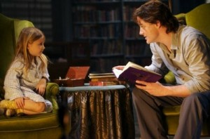 Silvertongue reading to a young Meggie. Both on green armchairs with a table in between them. Bookshelves can be seen behind.