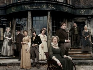 The Cast of Little Dorrit standing on steps in front of a old worn out building with glass windows.