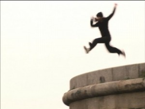 an actor leaping off a concrete structure into the air