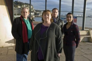 The cast of missing standing facing the camera with the view of the seaside behind