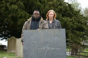 Tilda Swinton and Issac Julien behind a grey gravestone in a graveyard