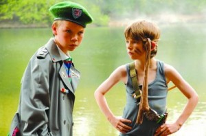 Will Pouter as Lee Carter wearing an army jacket and hat and Bill Milner as Will wearing a vest and band round his head