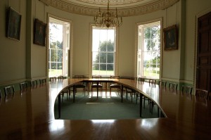 Picture of a boardroom with a large round table and chairs