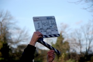 Picture of a clapper board being snapped by a crew member up towards the sky.