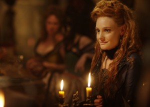 Romola Garai smiling away from the camera in a dark dress, two candles sit in front of her.