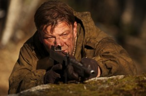 Sean Bean laying on the dirt staring into a gun looking at the camera