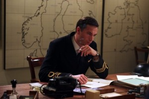 James D'Arcy as Ian Fleming sitting at a wooden desk with a map of the united kingdom pinned to the wall behind him