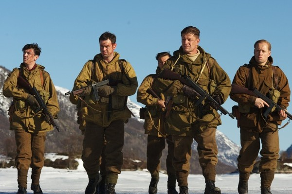 Age of Heroes cast members standing in a row in uniform with guns. Snowy mountains can be seen behind.