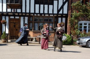 Behind the scenes of Chickens filming in Chilham- three actresses walking along the street in costume in front of a tutor style house