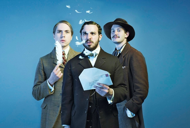 Joe Thomas (George), Simon Bird (Cecil) and Johnny (Bert) standing next to each other in front of a blue background staring at feathers