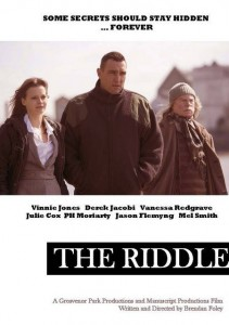 The Riddle Movieposter- Three cast members standing in a row with buildings faintly shown in the background. The Riddle is written in white on a black strip underneath.
