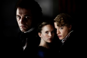 Matthew Rhys, Tamzin Merchant & Freddie Fox all staring into the camera against a black background