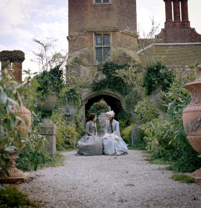 Bleak House filming at Cobham Hall - Gillian Anderson as Lady Dedlock and Anna Maxwell Martin as Esther sat on a bench in a formal garden, cobham hall can be seen behind