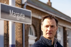 David Morrissey as Adrian at Margate train station with the sign behind him