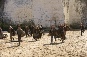Actors running towards the camera on botany bay beach, white cliffs behind