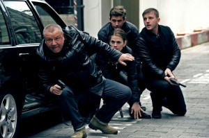 four actors crouched to the side of a black car with guns,