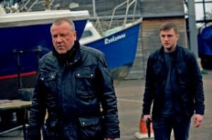 Ray Winstone and Ben Drew walking besides a boat yard with guns