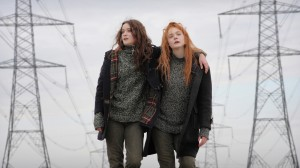 Ginger (right, Elle Fanning) and Rosa (left, Alice Englert) walking with their arms around each other in front of some pylons