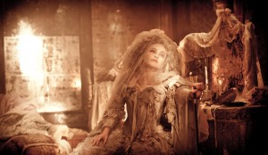 Helena Bonham Carter as Miss Havisham in a brides outfit sitting against a table