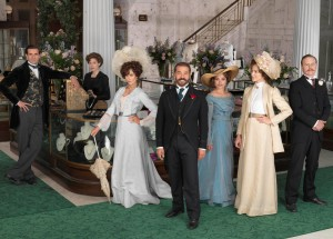 Mr Selfridge in the shop in front of the staircase. Other cast members are standing next to him.