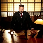 Jeremy Piven as Mr Selfridge leaning over a desk with windows behind