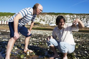 L-R Dougie (Karl Pilkington) and Kev (David Earl) on the beach. Kev has a crab in his hand and they are both looking at it