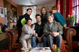 Ben Turnbell (Blake Harrison) sitting on a sofa with his family and friends