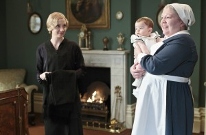 Joanne Froggatt as Anna Bates, Baby George and Di Botcher as Nanny West in a living room in front of a fire