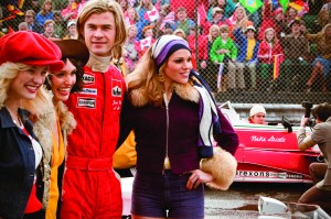 Chris Hemsworth as James Hunt posing with some ladies at a F1 racetrack