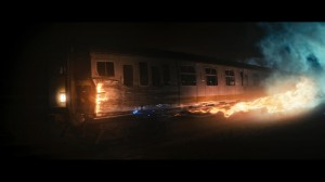 Train carriage on fire, coming off the railway tracks at night
