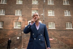 Dom Hemingway (Jude Law) in a suit smoking a cigarette with a large stone wall in the background